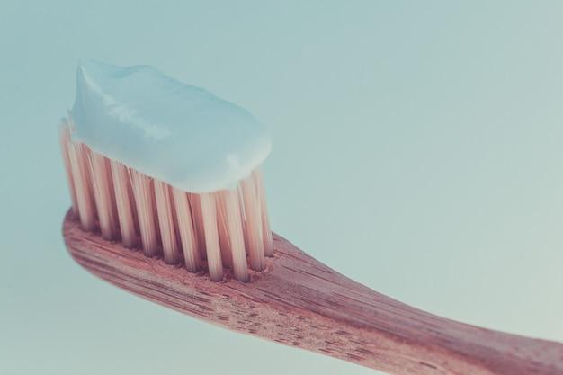 Beige tandborstel met witte tandpasta op blauw wit. geïsoleerd. detailopname.