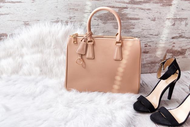 Beige tas en zwarte schoenen op wit bont