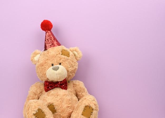 Beige teddybeer in een rode pet zit, een plek voor een inscriptie