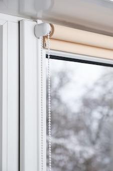 Beige verduisterend rolgordijn op het witte kunststof venster. luiken op het plastic raam.