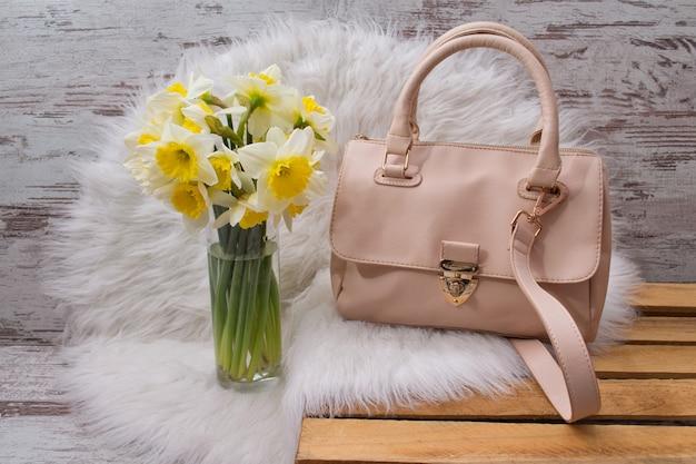 Beige vrouwelijke tas op wit bont, een boeket van narcissen. in de mode
