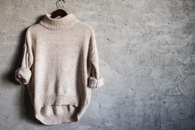 Beige warm shirt met lange mouwen op zwarte hanger op grijze muur