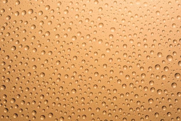 Beige waterdruppels op het glas