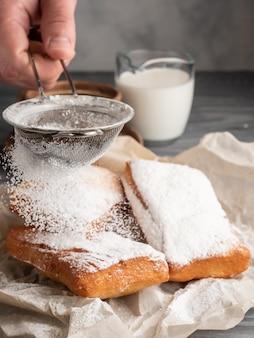 Beignet met poedersuiker op een houten lijst met koffie en melk wordt bestrooid die.