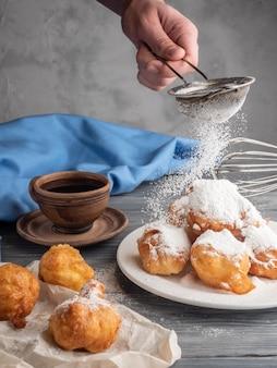 Beignet met poedersuiker op een houten lijst met koffie wordt bestrooid die.