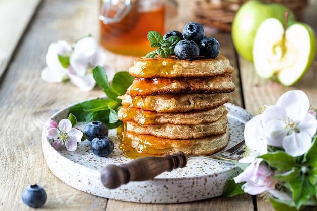 Beignets met appel en honing op een houten tafel.