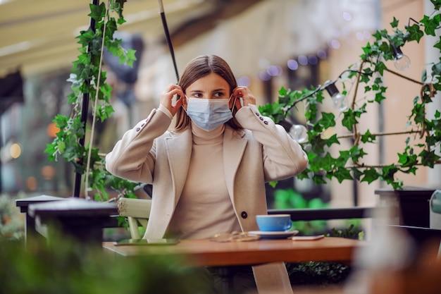 Beïnvloeder zittend in café en gezichtsmasker zetten tijdens corona-uitbraak. het is verboden om zonder masker in het openbaar te verblijven.