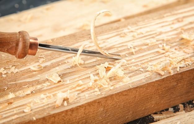 Beitel, houten planken en zaagsel in timmermanswerkplaats