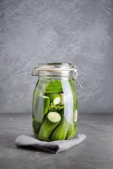 Beitsen en gisten komkommer in glazen pot met dille en knoflook op donkergrijs