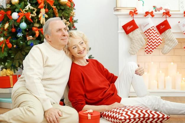 Bejaard echtpaar bij open haard in woonkamer ingericht voor kerstmis
