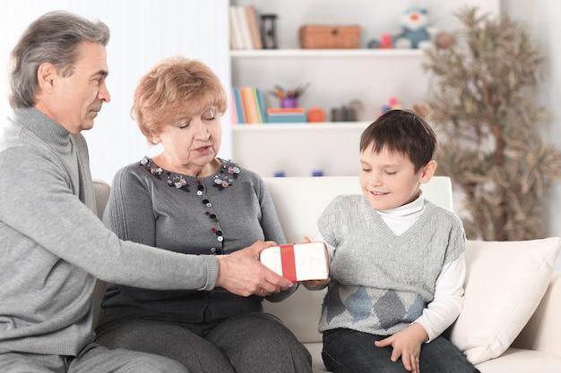 Bejaard echtpaar geeft een cadeau aan hun kleinzoon op zijn verjaardag