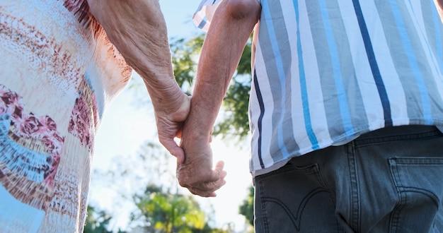 Bejaard echtpaar hand in hand en close-up