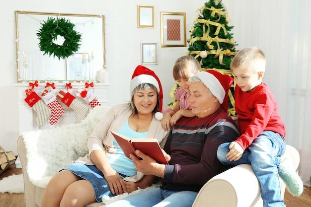 Bejaard echtpaar leest boek aan hun kleinkinderen in woonkamer ingericht voor kerstmis decorated
