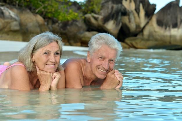 Bejaard echtpaar liggend op het strand in het water