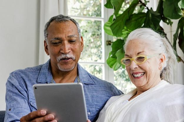 Bejaard echtpaar met behulp van een tablet op een bank