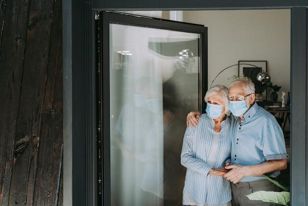 Bejaard echtpaar met beschermende gezichtsmaskers thuis tijdens covid-19 pandemische quarantaine - oude mensen in quarantaine respecteren sociale afstand en isolatie op verspreiding van coronavirusvirus