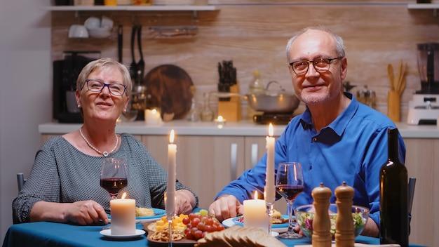 Bejaard echtpaar met een videogesprek in de keuken tijdens een romantisch diner, een feestelijke maaltijd etend. pov online internet moderne conferentie, chatten, communicatie, chatgesprek bellen via webcam