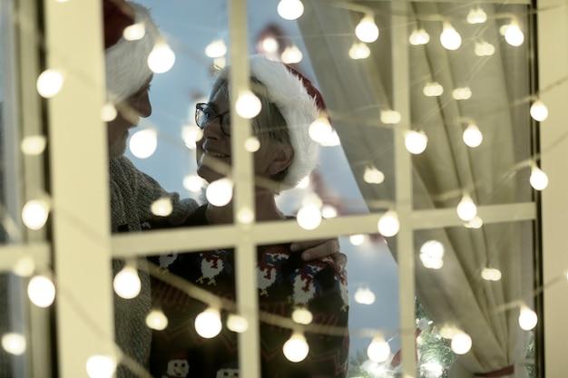 Bejaard echtpaar met kerstmutsen staat binnen achter het verlichte raam - vrolijk kerstfeest en uitdrukking van liefde voor twee gepensioneerde senioren die genieten van de kerstvakantie