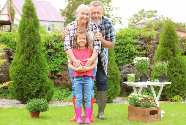 Bejaard echtpaar met kleindochter in tuin