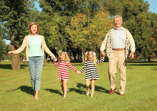 Bejaard echtpaar met kleindochters in park