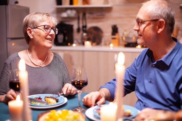 Bejaard echtpaar praten over geluk tijdens feestelijk diner. gelukkig vrolijk senior bejaarde echtpaar samen dineren in de gezellige keuken, genieten van de maaltijd, hun verjaardag vieren.