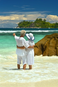 Bejaard echtpaar staande op het strand met uitzicht op de zee