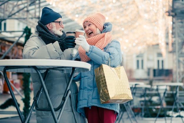 Bejaard echtpaar staat naast de ronde tafel op de nieuwjaarsbeurs en glimlacht terwijl ze hun papieren koffiekopjes laten kletteren