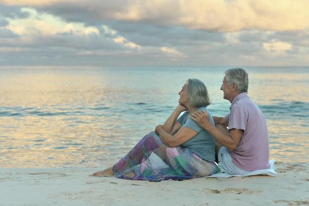 Bejaard echtpaar zittend op de kust en kijkt naar de zee