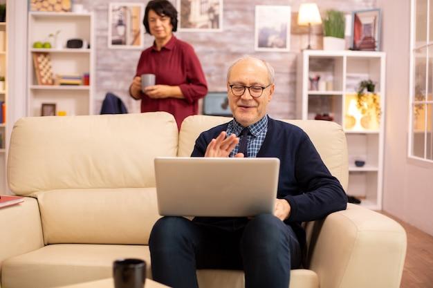 Bejaard oud echtpaar dat moderne laptop gebruikt om met hun kleinzoon te chatten. grootmoeder en grootvader met behulp van moderne technologie