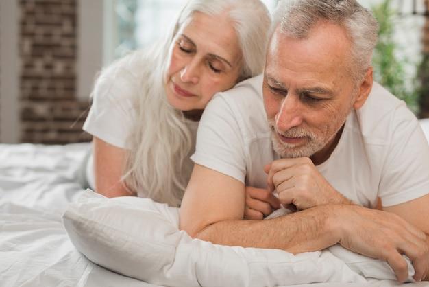 Bejaard paar dat in bed op valentijnskaartendag wordt gelegd