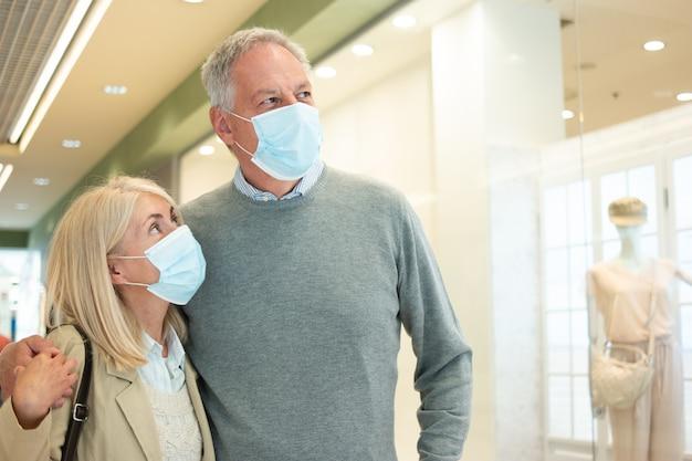 Bejaard paar dat in een winkelcomplex tijdens pandemie van coronavirus loopt
