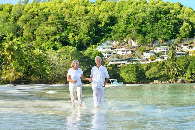 Bejaard paar dat op het strand dichtbij de zee rent