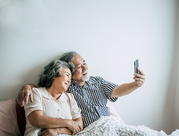 Bejaard paar dat smartphone gebruikt