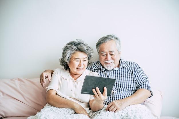 Bejaard paar dat tabletcomputer met behulp van