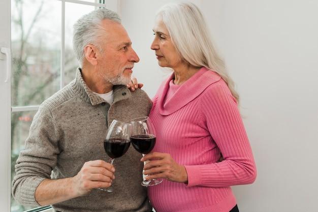 Bejaard paar dat van glas wijn geniet
