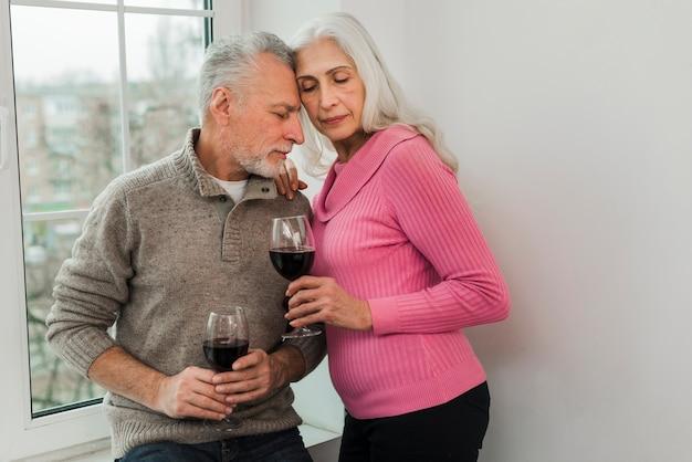 Bejaard paar dat van glas wijn samen geniet