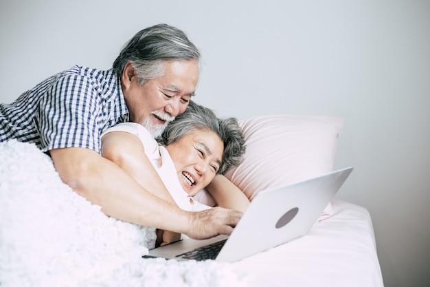 Bejaard paar die laptop in slaapkamer met behulp van