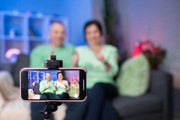 Bejaard paar die smartphone videoconferentie met kleinkind gebruiken terwijl thuis het liggen op bank in woonkamer. thuis genietend van het hogere familieconcept van de tijdlevensstijl. portret dat camera bekijkt.