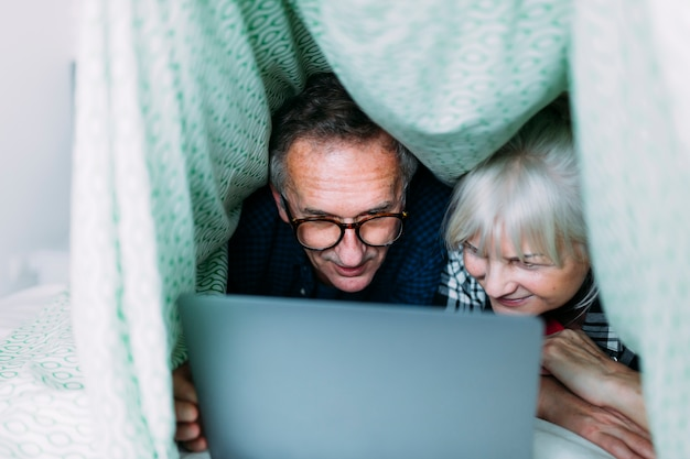 Bejaard paar in hol in bed met laptop