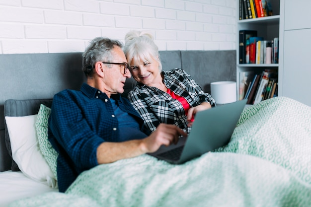 Bejaard paar samen in bed met laptop