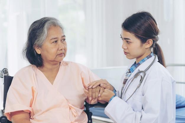 Bejaard wijfje die met arts glimlachen en hogere geduldige vrouw bezoeken bij het ziekenhuisafdeling