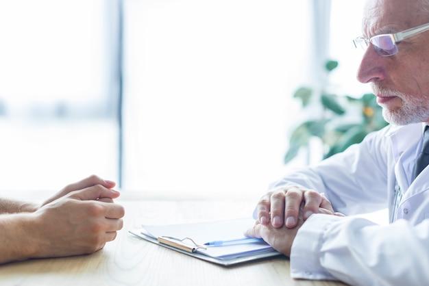 Bejaarde arts met patiënt op kantoor