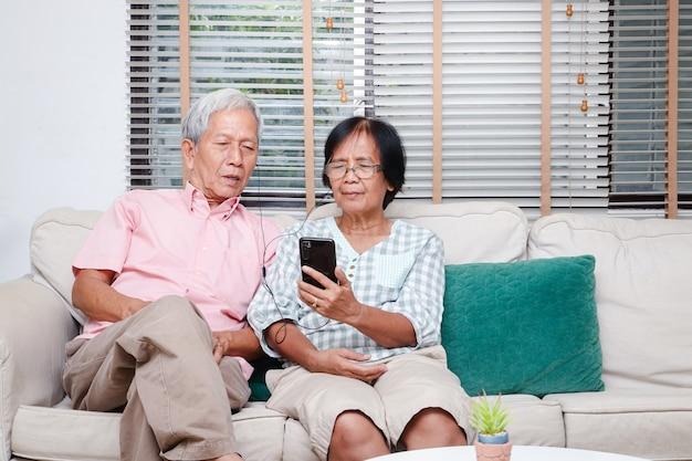 Bejaarde aziatische echtpaar zittend in de woonkamer houdt een smartphone om kinderen en kleinkinderen te begroeten