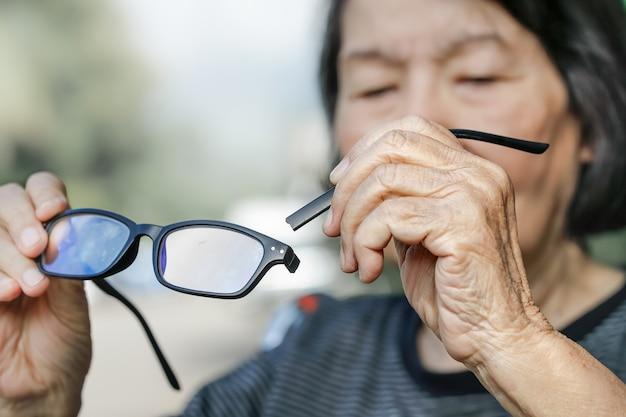 Bejaarde aziatische vrouw die gebroken glazen herstelt