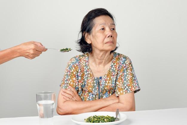 Bejaarde aziatische vrouw verveeld met eten