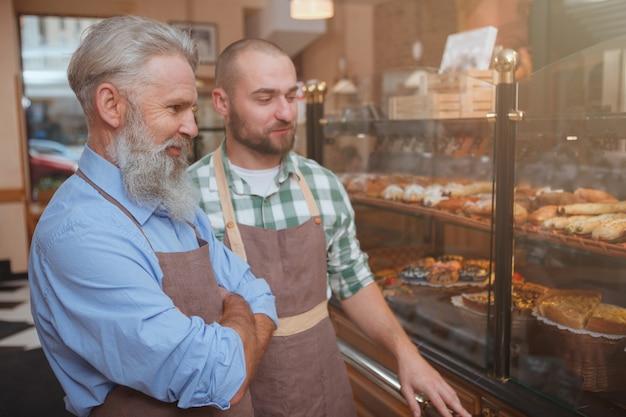 Bejaarde bakker en zijn zoon die samen bij hun bakkerijwinkel werken