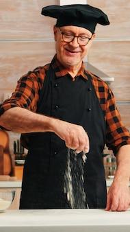 Bejaarde bakkersbloemtafel om heerlijke koekjes te bakken en te maken. gepensioneerde senior chef-kok met bonete en schort in uniform besprenkelen zeven zeven ruwe ingrediënten met de hand bakken zelfgemaakte pizza, brood