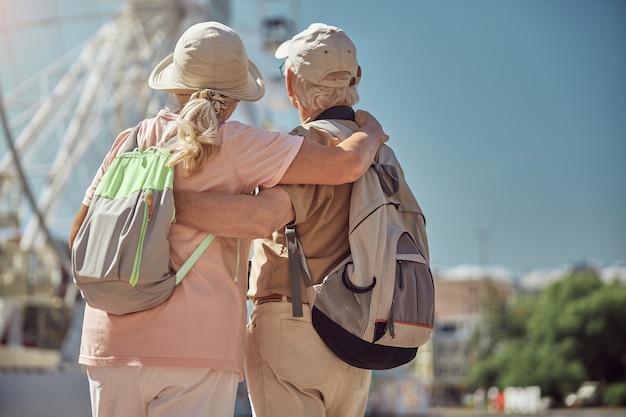 Bejaarde blanke dame en een grijsharige man die naar een toeristische attractie kijkt