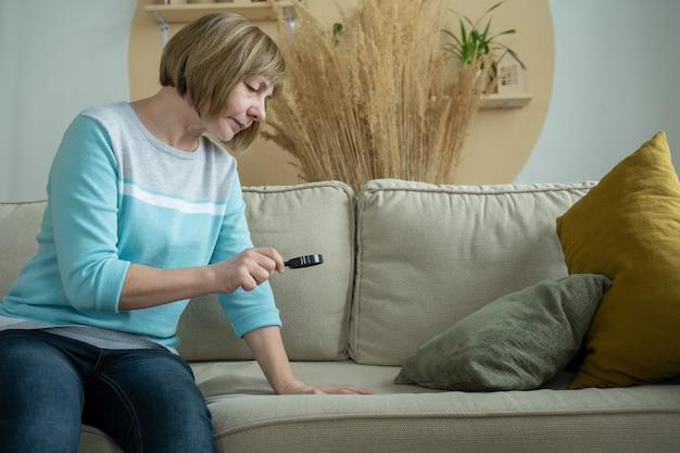 Bejaarde boos vrouw onderzoekt vlekken op de bank met vergrootglas