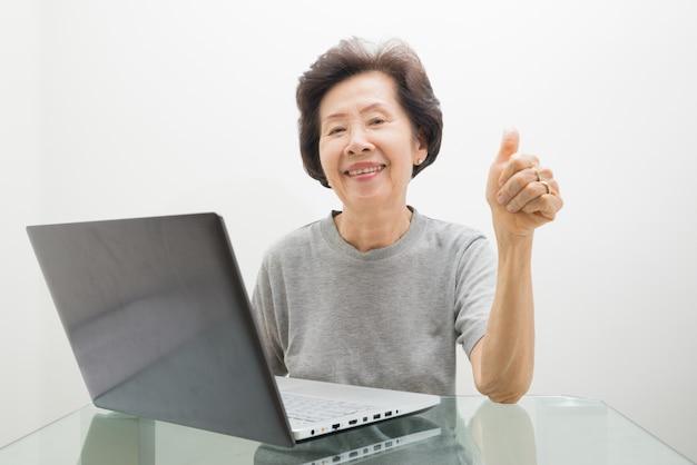 Bejaarde dame die met laptop werkt, die met laptop en duimen omhoog werkt